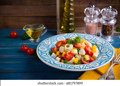 Fresh argentine salad of heart of palm (palmito), cherry tomatoes, yellow bell pepper, garlic and parsley on wood blue background
