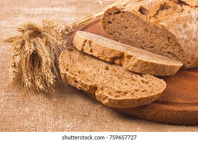 Fresh aromatic organic rye farm craft bread with ears at wooden board and sacking.