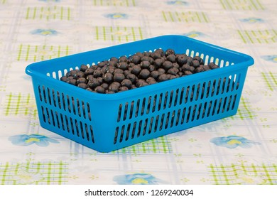 Fresh aronia berries in blue plastic container on a table.