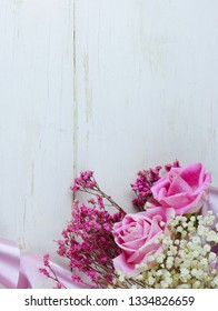 A fresh arrangement of pink roses and dried flowers with satin ribbon on rustic white washed wooden table. Shot from above. Vertical image for mother's day, weddings, anniversaries, or secretaries day