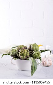 Fresh artichoke preparing for cooking with garlic, lemon and olive oil, kitchen interior.