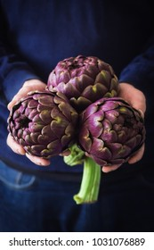 Fresh artichokes in male hands. Selective focus