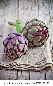 fresh artichokes on rustic wooden background