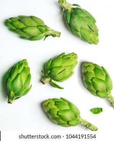 Fresh artichokes on white background, top view