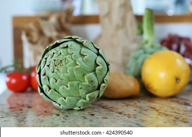 Fresh artichokes, potatoes, tomatoes and grapefruit in a kitchen mirroring in the counter