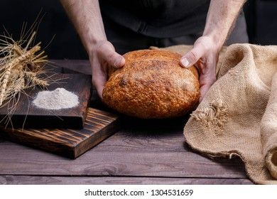 Fresh artisan bread in male hands. The concept of healthy food and traditional bakery. Rustic.