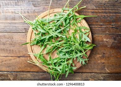 fresh arugula close-up on a round cutting board. traditional Italian seasoning