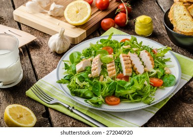 Fresh arugula, lamb's lettuce salad with grilled chicken and nuts