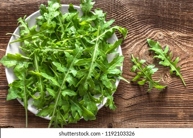 Fresh arugula leaves, green vegetables, leafs of rucola on plate on wooden background