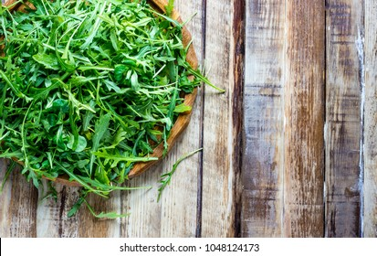 Fresh arugula leaves on wooden bowl, rucola. Arugula rucola on wooden old background. Arugula rucola for salad. Top view, blank space.