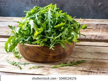 Fresh arugula leaves on wooden bowl, rucola. Arugula rucola on wooden old background. Arugula rucola for salad. Selective focus, blank space.