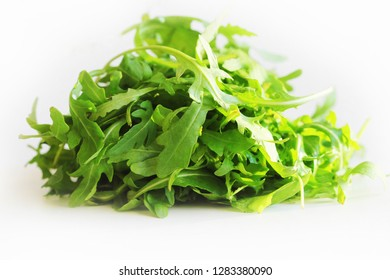 Fresh arugula leaves rucola on white background .