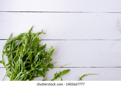 fresh arugula salad leaves lying on a wooden table