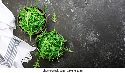 Fresh arugula salad leaves in two clay bowls on black rustic background with copy space for your design. Healthy diet food concept. Restaurant menu, cooking blog template. Minimalism style composition