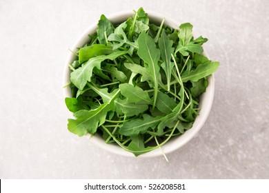 fresh arugula salad on a grey stone background.