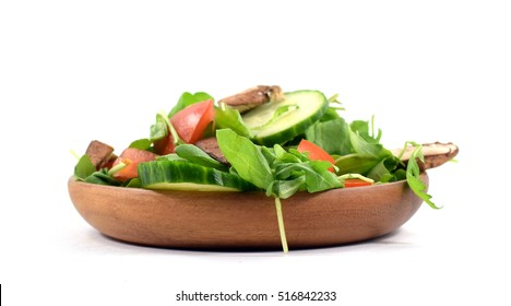 Fresh arugula salad with raw mushrooms, tomato, and cucumber on wood plate - isolated