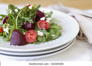 A fresh arugula salad with tomatoes and beets.