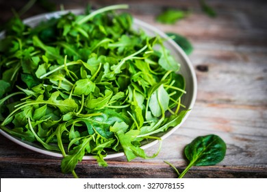 Fresh arugula and spinach salad on rustic background