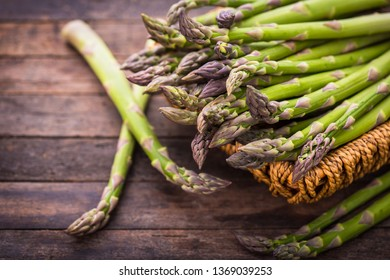 Fresh asparagus in the basket on the wooden table