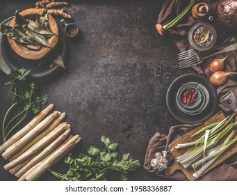 Fresh asparagus bunch on dark rustic table with fresh ingredients and kitchen utensils .Top view. Frame. Cooking preparation