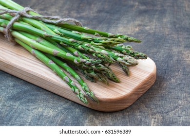 Fresh asparagus sheaf. White,grey wooden background. Copy space. Closeup photo. Top view.