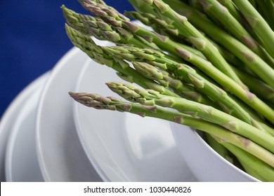 Fresh asparagus tips on a stack of white plates