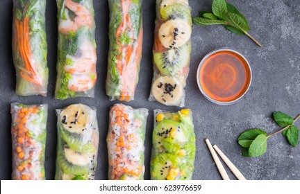 Fresh assorted Asian spring rolls with shrimps, vegetables, fruit, rustic concrete background