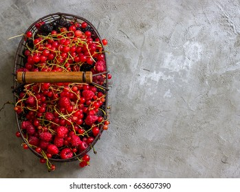 Fresh assorted fruit and berries in a basket on a concrete background. Top view.