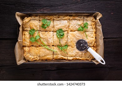 Fresh australian Meat pie with cilantro on a wooden table. Rustic style, top view.