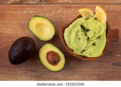 Frische Avocadocreme in brauner Schüssel und frisch geschnittene Avocados auf braunem Holzhintergrund. Draufsicht. Kopiert Platz. Vegetarisches Lebensmittelkonzept, Vintage-Stil, Avocado-Hintergrund.