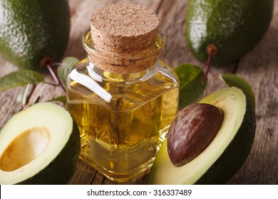fresh avocado oil in a glass bottle on a wooden table macro, horizontal
