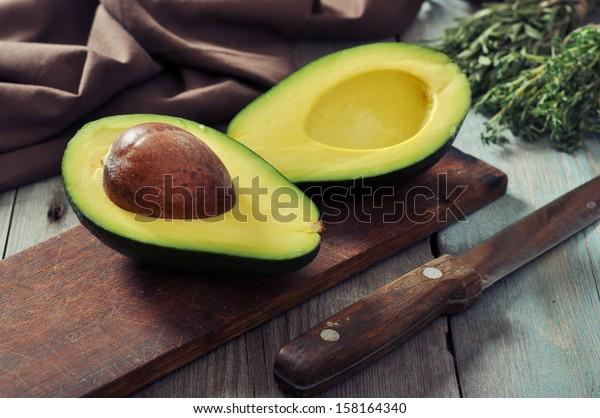 Свежий авокадо на разделочной доске на деревянном фоне