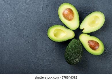 Fresh avocado on dark background. Vegetarian  food concept. Top view.