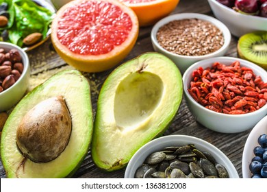 Fresh avocado and other healthy food. Organic breakfast containing super foods. Vegan nutrition like nourishing fruit, assorted berries and seeds.