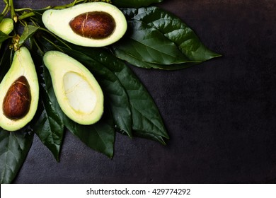 Fresh avocado palta with leaves on black background. Guacamole ingredient. Vegetarian or healthy eating. Healthy fat