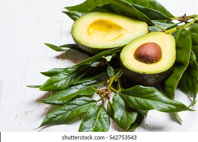 Fresh avocado palta with leaves on white background. Guacamole ingredient. Vegetarian or healthy eating. Healthy fat