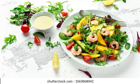 Fresh Avocado, Shrimps, Mango salad with lettuce green mix, cherry tomatoes, herbs and olive oil, lemon dressing. healthy food