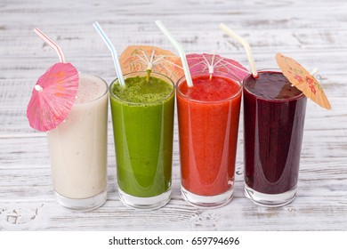 Fresh avocado, strawberry, blueberry and banana drinks on wooden table, assorted protein cocktails with fresh fruits. Close up