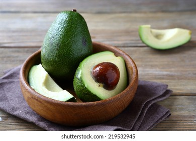 Fresh avocado in a wooden bowl, food on a wooden background