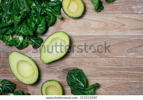Fresh avocados and green leaves of salad on the wooden table