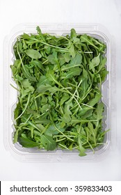 fresh baby arugula in a plastic container on a white background, vertical, top view