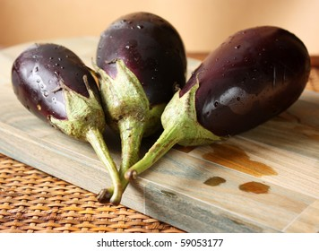 Fresh Baby Eggplants over cutting board