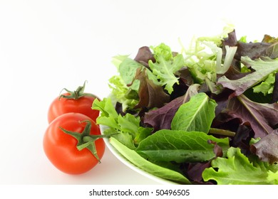 Fresh baby green salad and tomatoes on white background