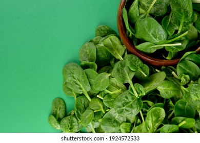 Fresh baby spinach leaves on a green background stock images. Fresh green spinach in a wooden bowl top view. Healthy leafy vegetables stock photo