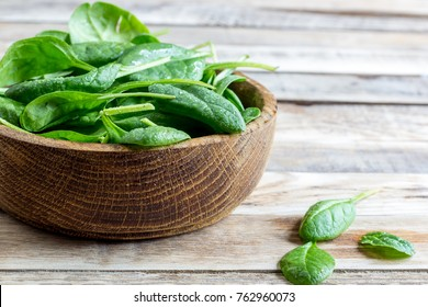 Fresh baby spinach in a wooden bowl on rustic wooden background, selective focus