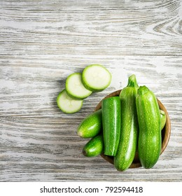 Fresh baby zucchini in a bowl on white shabby wooden background. Top view, space for text.