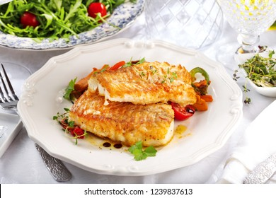 Fresh backed codfish filet on white table