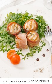Fresh bacon rolls served with arugula salad on white plate