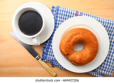Fresh Bagel with coffee over wooden table background
