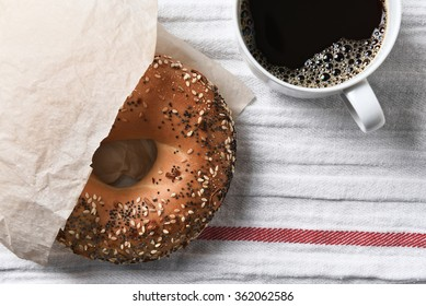 Fresh bagel and hot cup of coffee on a tea towel. High angle view in horizontal format.